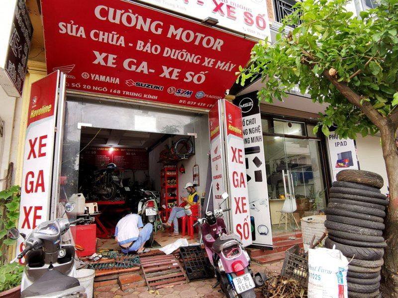 越南河內市允許部分行業自16日中午起恢復經營,圖為一家機車行在歇業2個月後重新開門做生意,店內師傅正在幫客人修機車。中央社