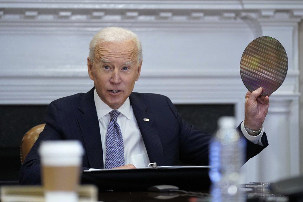 美國總統拜登4月與企業領袖進行線上會議討論晶片供應問題時,拿起一片矽晶圓。  美...