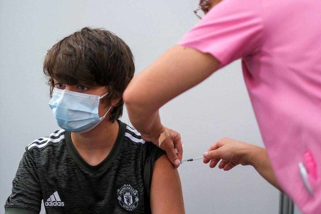 葡萄牙塞沙爾一名男孩11日接種第二劑輝瑞疫苗。路透