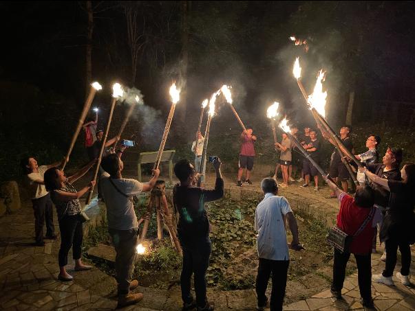 遊客手持竹竿,到茶山秘境「水火同源」,感受鄒族傳統文化。 圖/莊祖銘 攝影