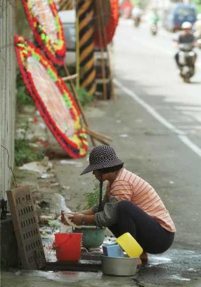 東勢地區在大地震後第四天依舊沒水沒電,部份民眾在無水可用的情況下,汲取水溝水用來洗滌鍋盤。圖/聯合報系資料照片