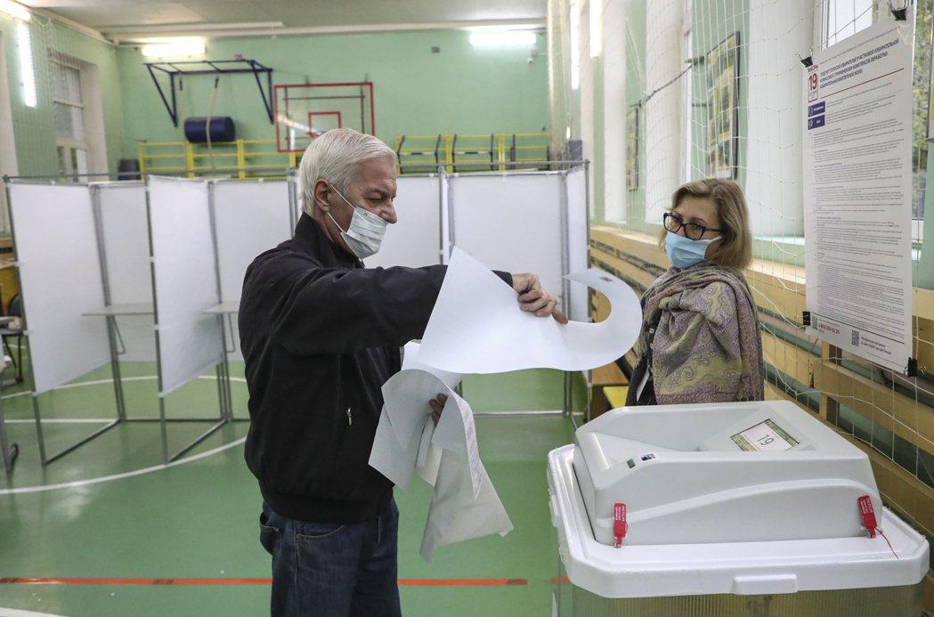 俄羅斯國會大選將舉行3天,圖為17日莫斯科一位民眾準備將選票放入票匭。歐新社