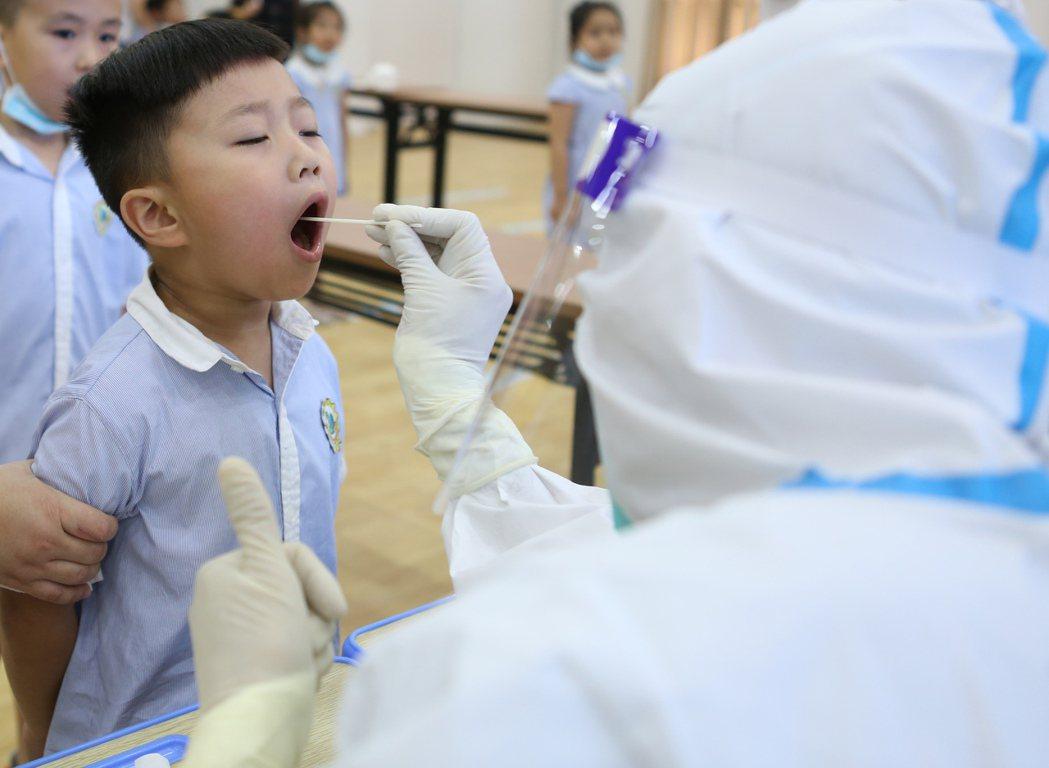 大陸的核酸檢測費用再降。圖為福建對各級各類學校學生實施核酸檢測。(新華社)