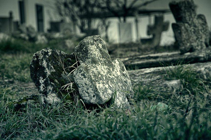 病人母親的墓園已毀損,雜草纏繞著死者骨骸中的頭骨,就是頸椎的地方。墓園乏人整理,又似乎遭災害或外力破壞,才會造成墓園殘破不堪。圖片來源:Ingimage