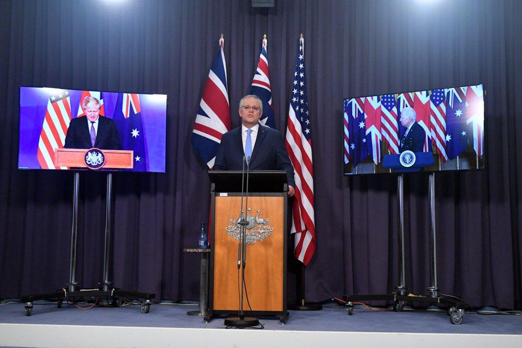 美國總統拜登(右)、英國首相強生(左)和澳洲總理莫里森(中)十六日透過視訊記者會...