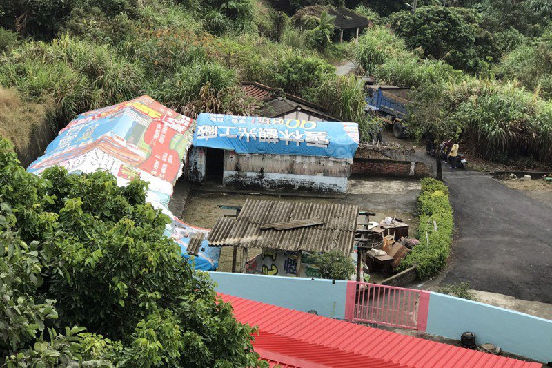 台南官田區大坵大井部落有1戶全家11口擠在破爛的土角厝,屋頂漏雨10多年,回收選舉廣告帆布蓋了5、6層,令志工印象深刻。 圖/台南市勞工局提供