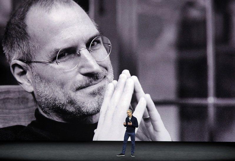 蘋果公司執行長庫克(前)17日在員工大會上,回應薪資公平性等問題。圖為庫克2017年在該公司已故創辦人賈伯斯的巨幅照片前發表演說。美聯社