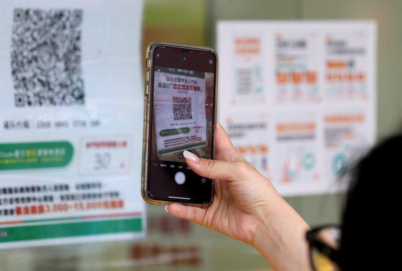 防疫期間,民眾透過手機拍場所代碼,經由簡訊實聯制留下走過的場所足跡。圖/本聯資料照片