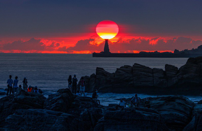 中秋節前後從基隆外木山海岸,可以看到太陽從基隆港嘴外堤燈塔後方升起,形成國門燈塔懸日美景。圖/張隆提供