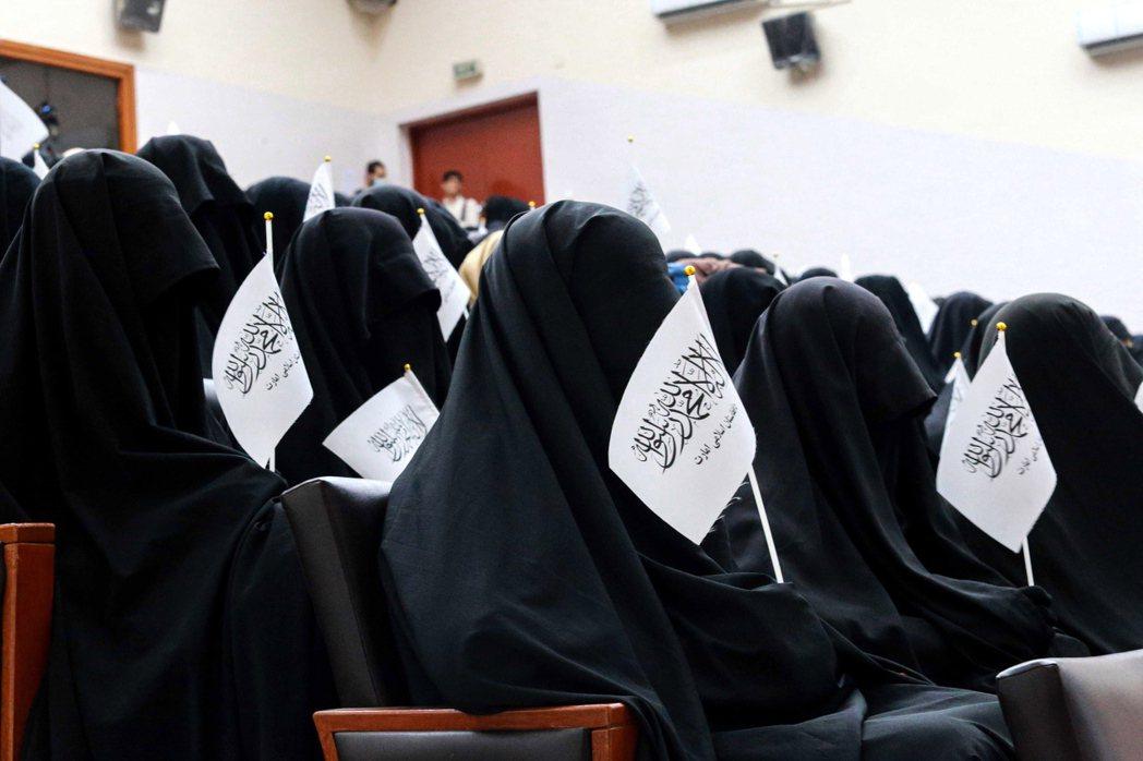 穿罩袍的阿富汗女學生11日在喀布爾拿著神學士旗幟聆聽女性演講。(歐新社)