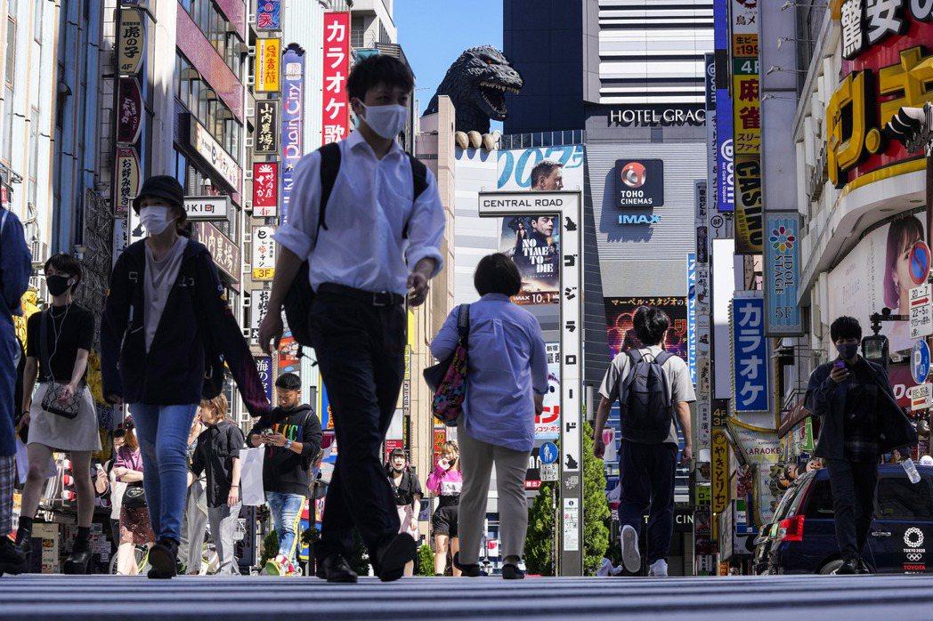 日本東京戴口罩民眾20日經過新宿街頭。美聯社