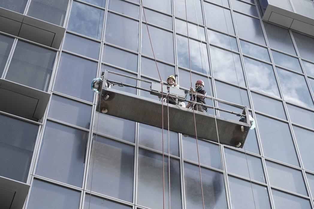 藝人吳鳳與吊籠操作人員一起介紹吊籠安全防護。 台北市勞動局/提供
