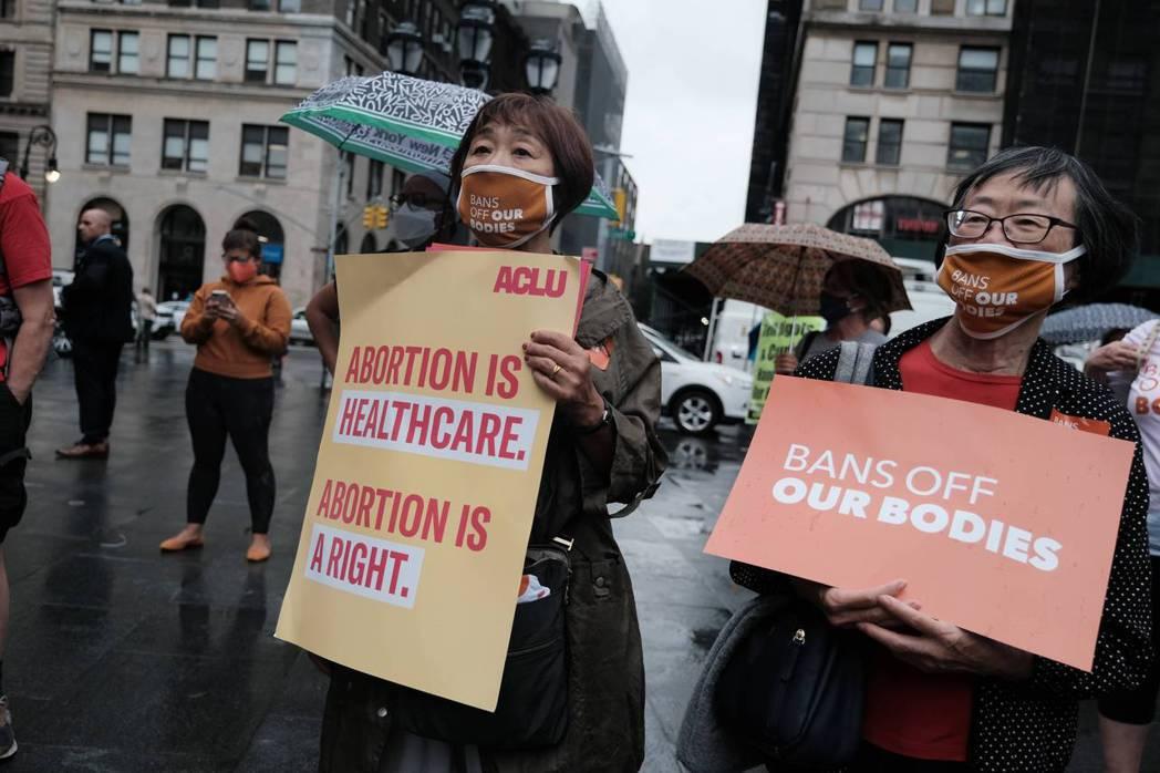 圖為美國各地群眾針對八號法案在街頭上舉牌抗議。 圖/法新社