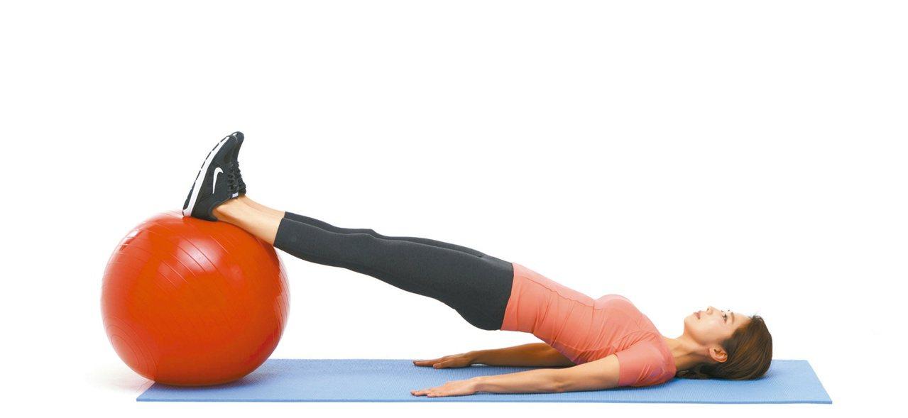 2.臀部夾緊,再用腳後跟壓抗力球,並同時將臀部抬起,維持10秒再放下。圖/聯經出...