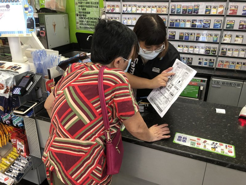 便利商店員工化身客服人員,教長輩如何進行紙本五倍券預約登記。記者鍾維軒/攝影