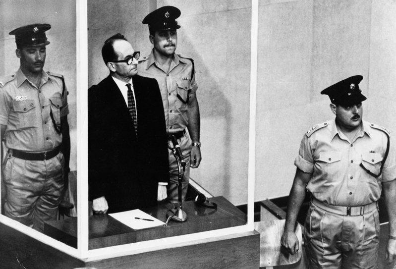 1961年被以色列情報機構從阿根廷抓回的前納粹黨衛軍少校艾希曼(黑西裝者),在耶路撒冷大審判中出庭。美聯社資料照