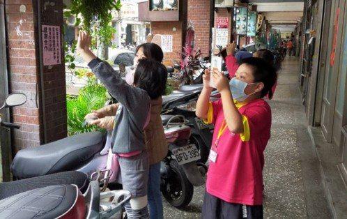 上《一支麥克風》課程的孩子們在社區中攝影。 圖/FUN心在台北提供