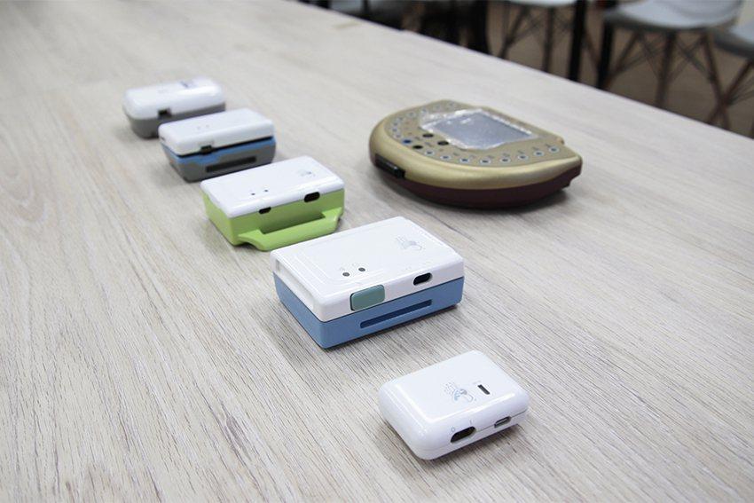 中大研發團隊歷代腦波機展示,第七代外觀只有菸盒大小,兼具科技美學造型(如右前方所...