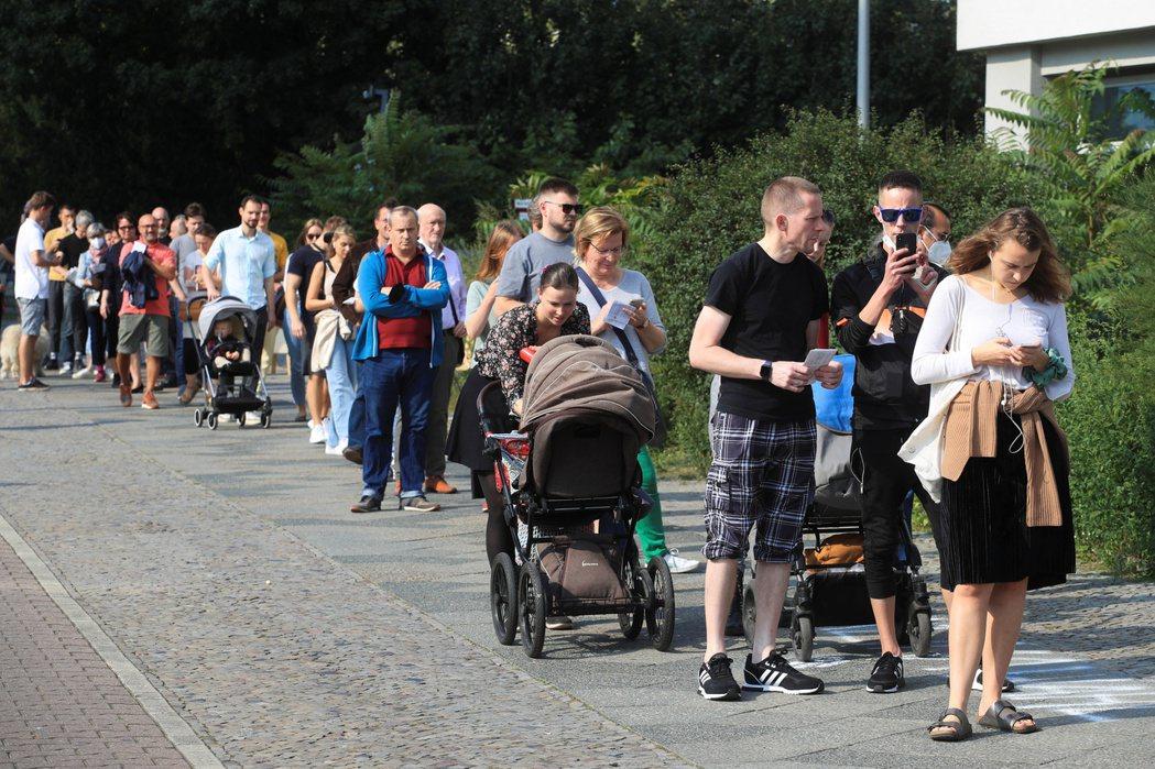 德國26日舉行國會大選,民眾在柏林一處投票所外排隊準備投票。(路透)