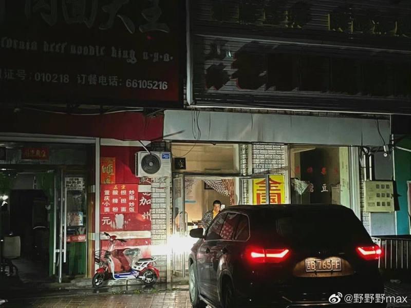 大陸東北某居民區一片漆黑,有人用車頭燈當照明。(新浪微博)
