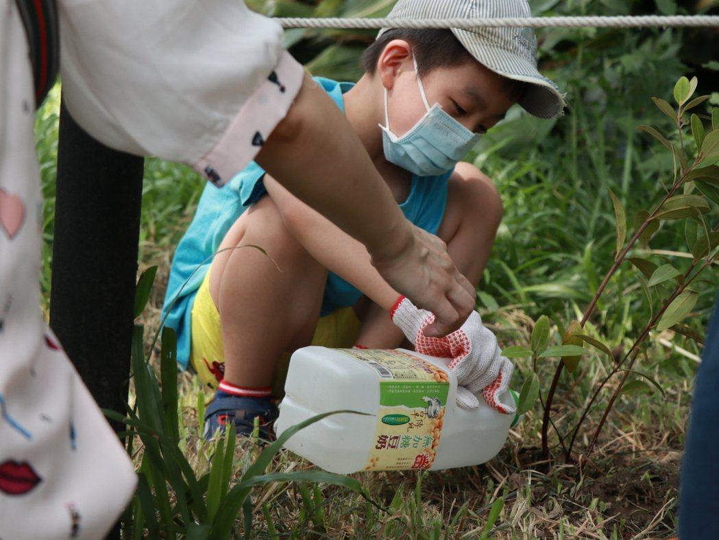 參與種樹活動的小朋友,在志工的指導與爸媽的協助下,攜手種下小樹。國泰金控/提供
