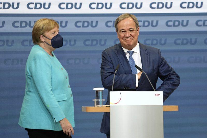 德國國會大選廿六日投票截止、媒體發布出口民調後,基民黨總理候選人拉謝特(右)在位於柏林的黨總部向支持者發表談話,總理梅克爾(左)站在一旁。(美聯社)