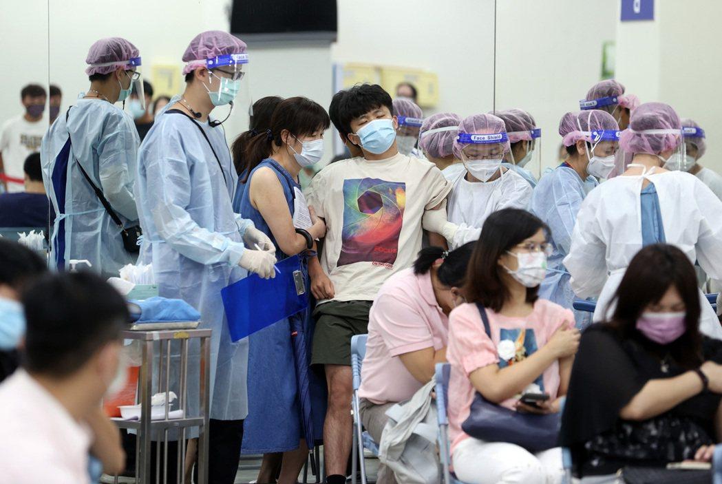 台北田徑場注射站已開始施打BNT及AZ疫苗第二劑,打BNT民眾非常踴躍,但仍有民眾發生暈針現象,護理人員趕緊將民眾推到旁邊休息。 圖/聯合報系資料照