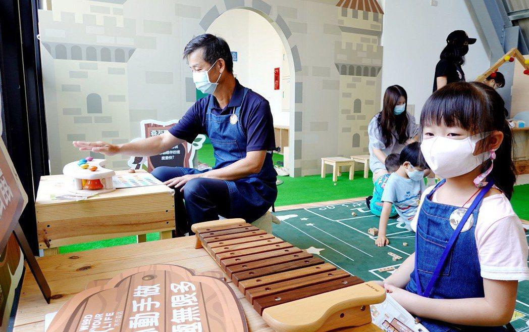 童心未泯的歐德集團董事長陳國都(左),看到這麼精緻有趣的木作遊具,也忍不住玩樂起...