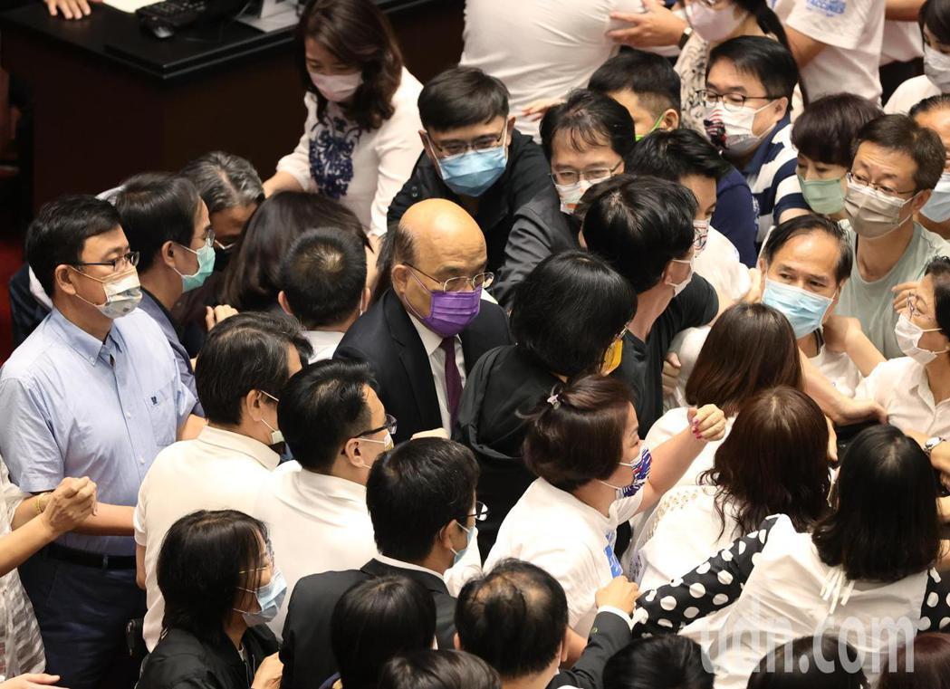行政院長蘇貞昌(中)今天上午前往立法院進行施政報告,在藍委力阻、綠委護航的擁擠局...