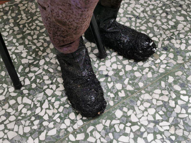 黃萬枝的工作鞋沾滿黑色瀝青,他卻認為方便工作。記者卜敏正/攝影