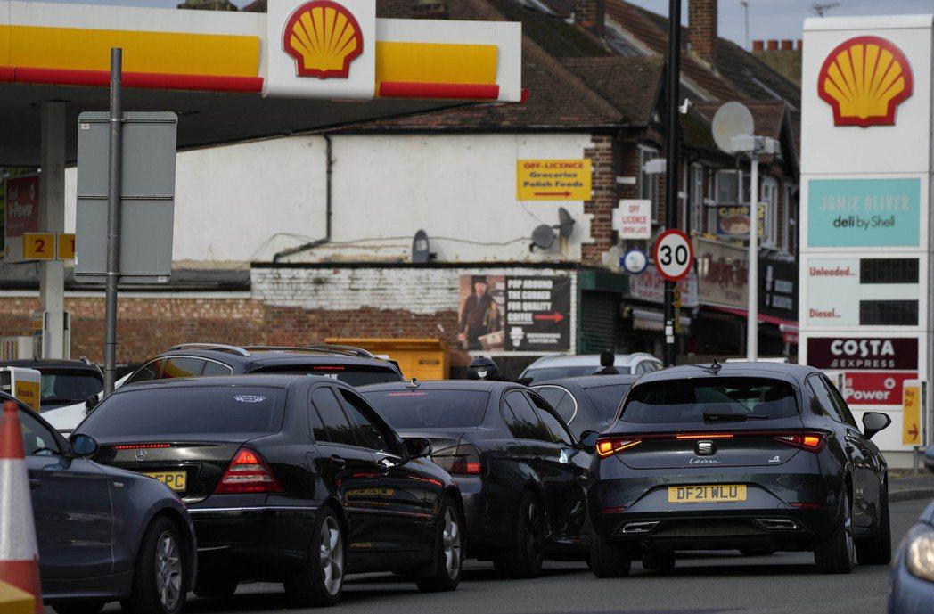大批車輛28日在倫敦一座加油站前排隊搶著加油。(美聯社)