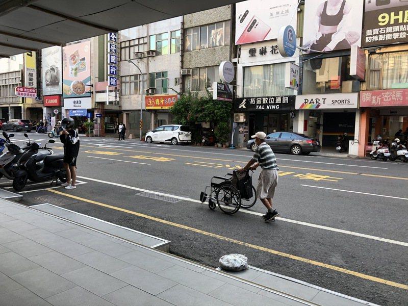 台灣各縣市騎樓常見高低不平,造成不少老幼或行動不便者無法行走。圖中老人就因騎樓高低不平,在馬路邊推著輪椅行走,險象環生。記者何定照/攝影