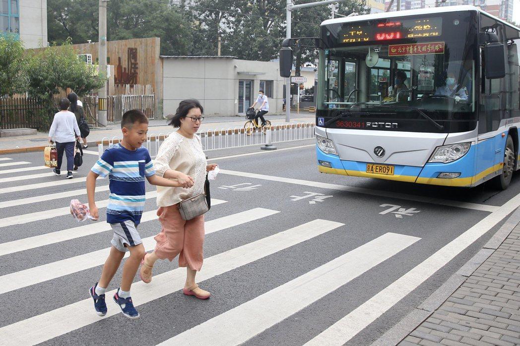 圖為中國北京行人通過馬路示意圖。 圖/中新社
