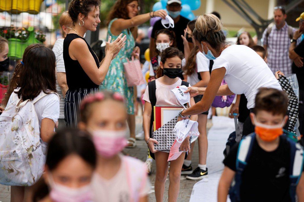 圖為以色列的學校人員發口罩給剛放完暑假返回校園的學童。 圖/路透社