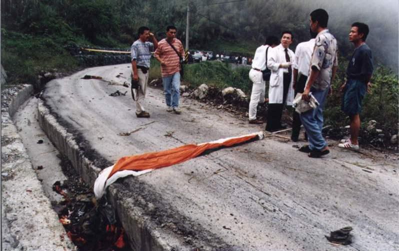 雙座戰機中其中一名飛官殘缺不全的屍體,連同降落傘掉落在在產業道路上,降落傘並未打開。圖/聯合報系資料照片