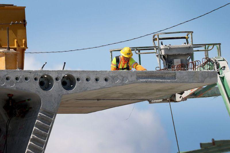 美國總統拜登提出的基建法案內容包括翻修全國老舊道路、橋梁、管線、港口等。圖為一名工人正在邁阿密一處橋梁工地工作。法新社