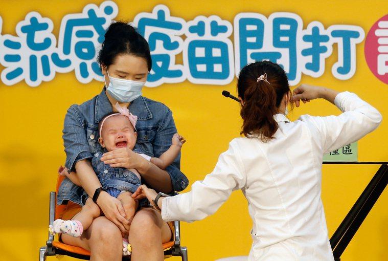 衛福部疾病管制署舉行「守護我們所愛的人」公費流感疫苗開打記者會,邀請一對父母帶著...