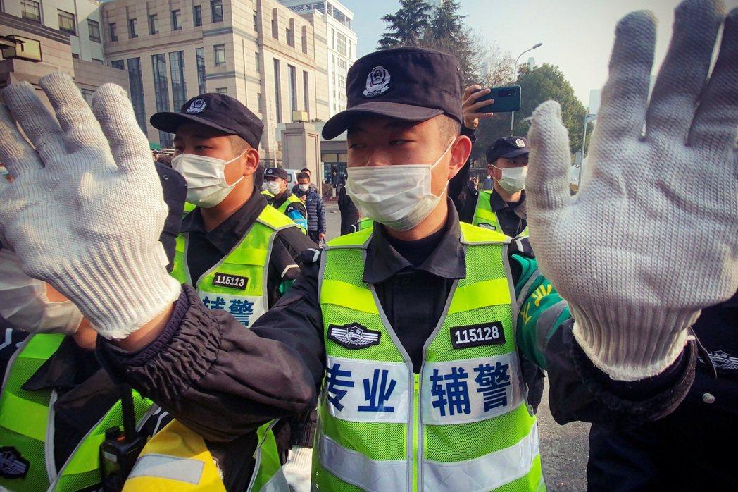 張展判刑當天,法庭外阻止媒體拍攝的中國輔警。 圖/法新社