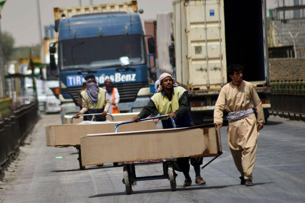 圖為內戰戰告一段落後,往來於伊朗-阿富汗邊境,向阿富汗「運送棺材」的邊境車隊。...