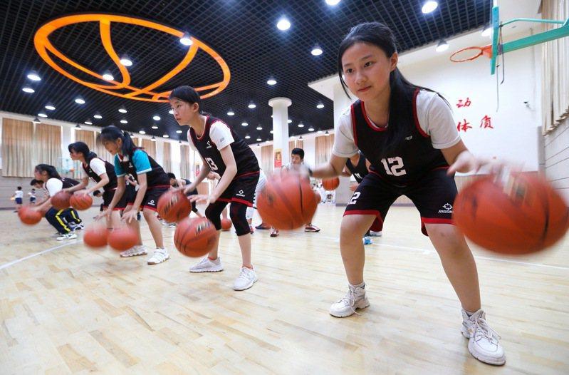 大陸中小學體育課增加時數,中學聯考也增加體育科的分值。圖為山東的學生們在體育課練習籃球運球。新華社