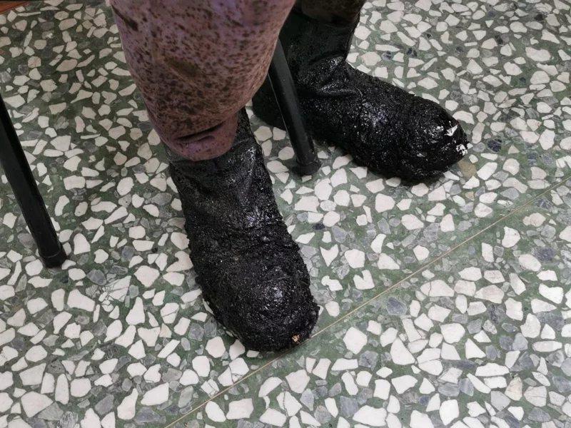 黃萬枝的工作鞋沾滿黑色瀝青,他卻認為方便工作。 圖/卜敏正 攝影