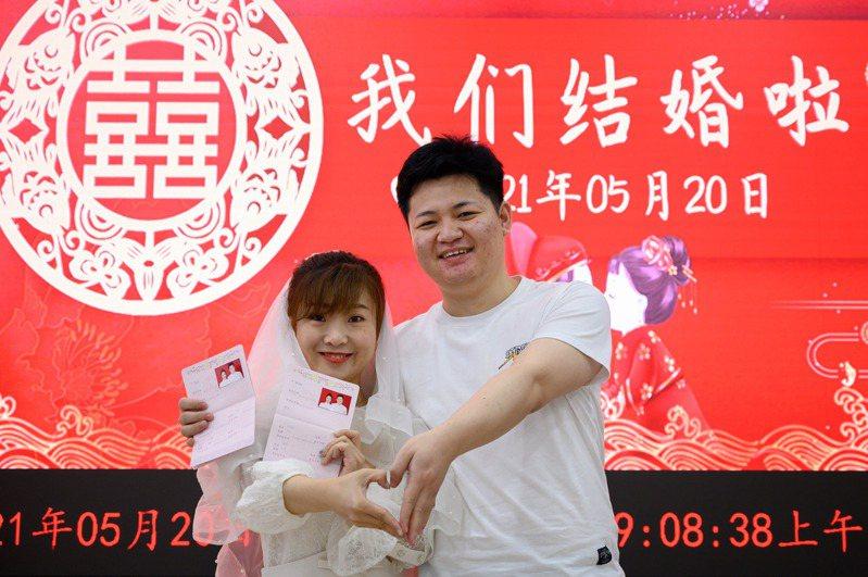 一對新人在婚姻登記處辦理結婚證,並拍照留念。中新社