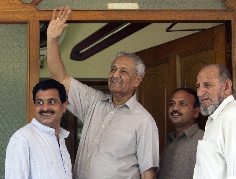 巴基斯坦核子科學家卡迪爾汗2009年在伊斯蘭馬巴德的自宅,對門外的記者揮手,當時他身邊都是安全人員。路透