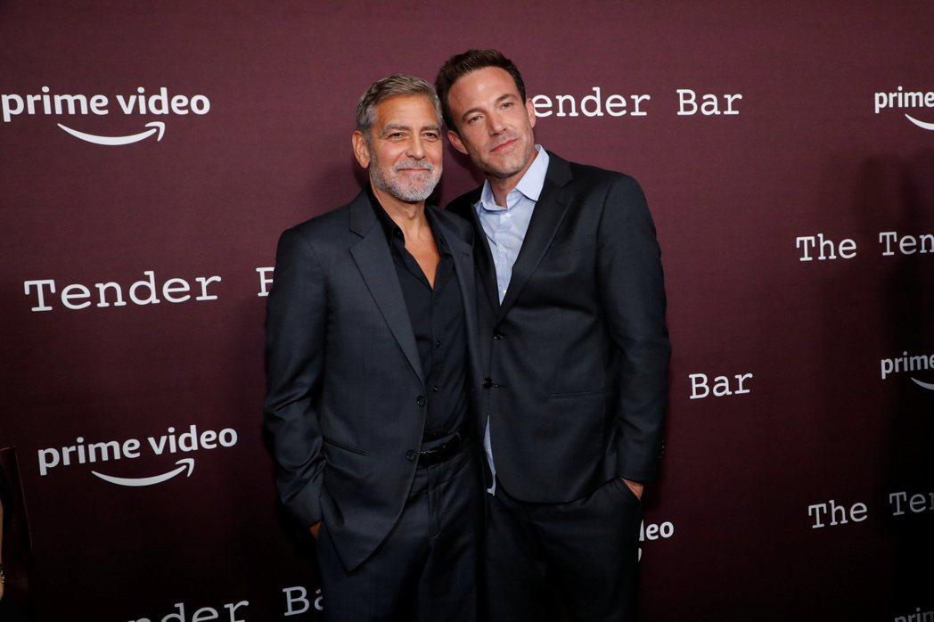 喬治柯隆尼(左)與班艾佛列克在「溫柔酒吧」首映會上合照,不見班的女友。(路透資料