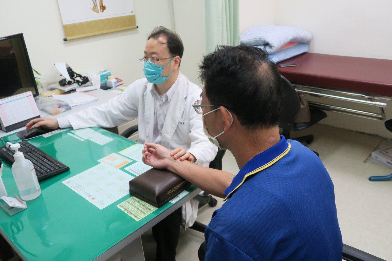 衛福部彰化醫院中醫師張煒東為「秋乏」病人把脈診治。 圖/簡慧珍 攝影