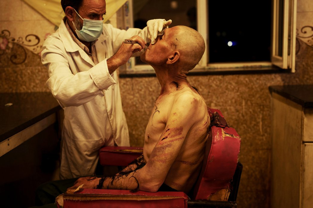 塔利班掌權後強調將嚴格控制毒品問題,圖為一名工作人員正幫被拘留的吸毒者刮鬍子。 ...