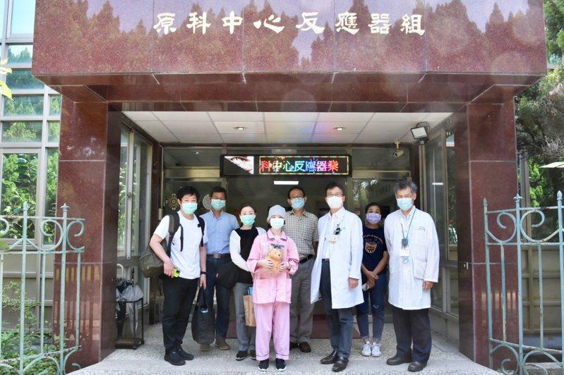 罹患惡性腦瘤的日本女孩(中)在清大硼中子捕獲中心治療結束後,接受醫療團隊送上的畢業方帽小熊。圖/清大提供