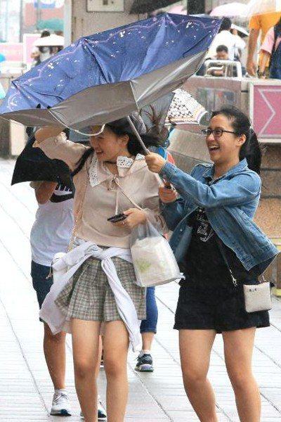 颱風來襲前,路上行人的傘都被吹花。圖/聯合報系資料照