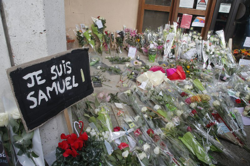 民眾在山繆帕第任教的學校外放置悼念花束,有海報寫著「我是山繆」。(美聯社)