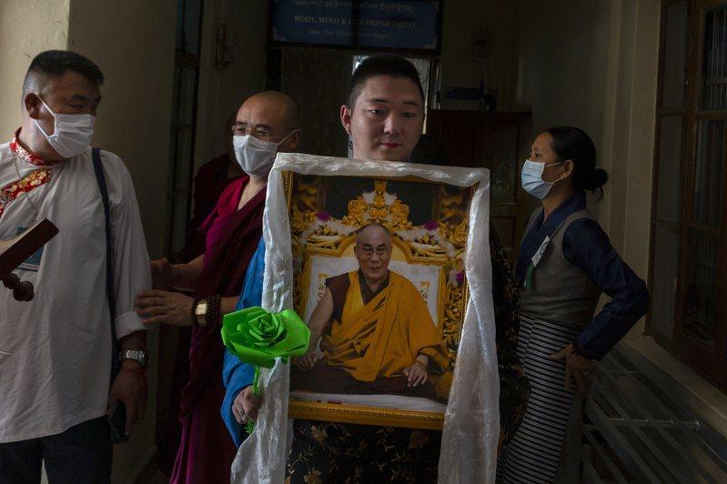 川普政府任命西藏事務協調員,政治分析家認為意在加劇中印緊張關係;圖為流亡印度的藏民舉著達賴喇嘛的畫像。(美聯社)